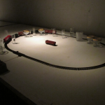 """Partitura"", 2010/2011, electric train, rails, rods, bottles, cups and wood, variable dimensions"
