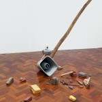 ''Brasília Broadcast'', 2006—2015  Wooden flagpole, sound archive, loudspeaker, mp3 player, electric power, steel wire, metal structure, bricks, stones and tools, variable dimensions.