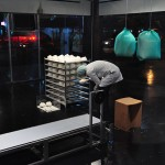 """Incubator"", 2014, installation/ performance, machine to fill balloons with styrofoam balls, funil, conveyor belt, stacking rack to place the balloons, polystyrene bead bags, various sizes according to space, performers Cláudio Tobinaga and Leandra Espírito Santo, filming and editing Eloi Mattar"